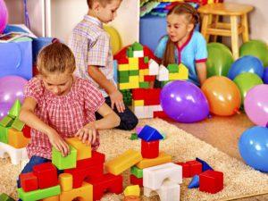 Group children game blocks in kindergarten . Balloons on floor. Top view.